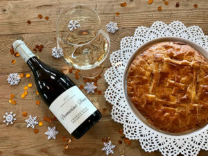 A bottle of Domaine Divio Chardonnay on a table with a glass of wine and freshly baked pie.