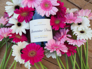 A bottle of Domaine Divio Pinot Beurot on a table surrounded by daisies.