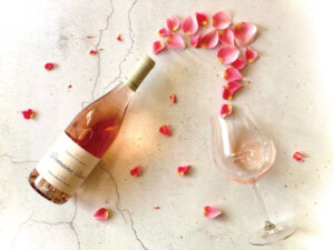 Rose petals on a table next to a bottle of Domaine Divio Rosé.